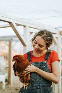 woman carrying hen